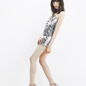 Model posing in silver sequin dress with highlighted brown hair.