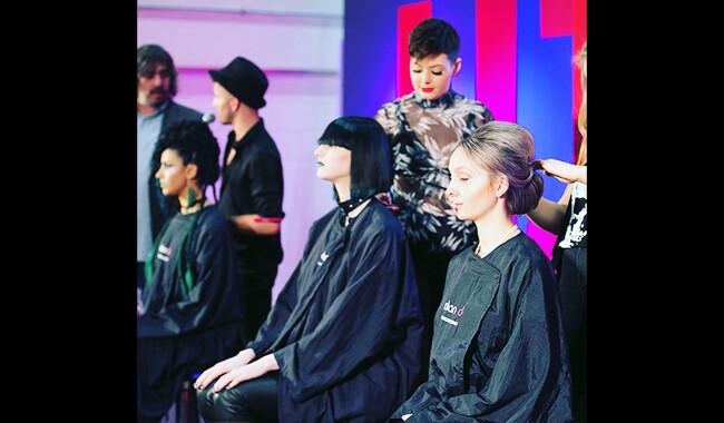 Three hair models having their hair cut.