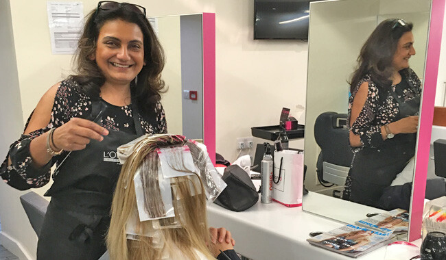 Alan d hairdressing teacher Sejal putting highlights in a womans hair.