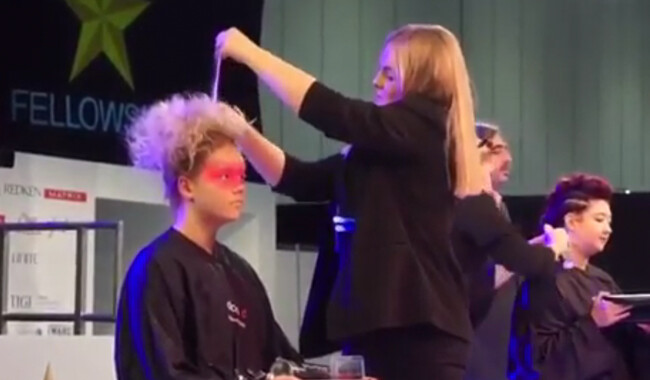 Alan d student styling a womans hair at the Salon International Exhibition.