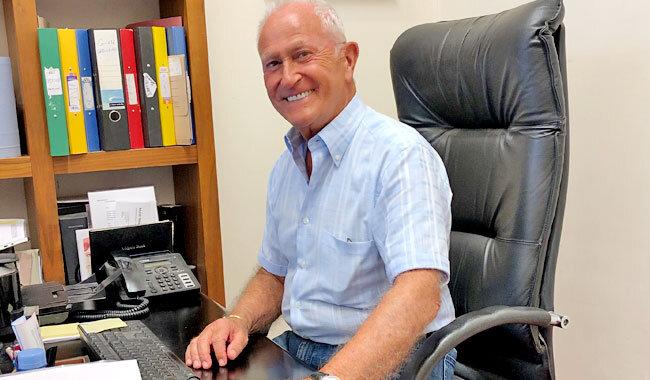 Alan d founder Alan Hemmings sitting at computer desk smiling.