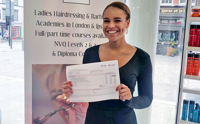 Student smiling whilst holding an Alan d hairdressing certificate.