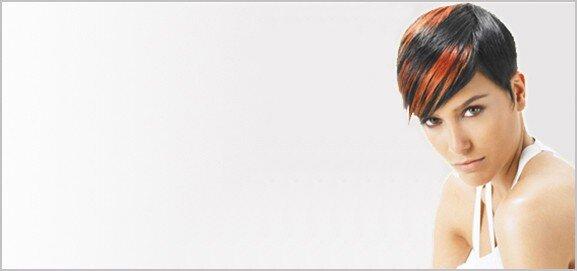 Female hair model with short dark brown hair and orange highlights.